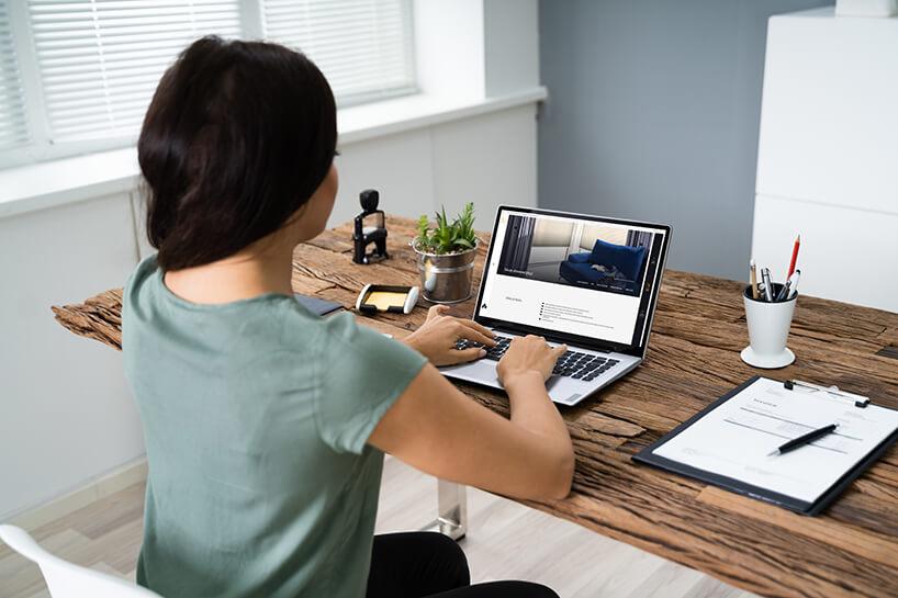 kobieta podczas obsługi komputera przy drewnianym stole