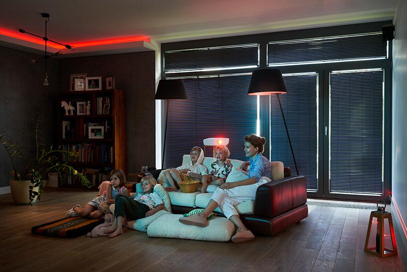 czwórka dzieci zmamą podczas oglądania filmu na tle zasłoniętych okien ciemnymi żaluzjami