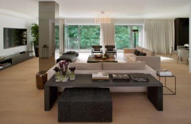 duży przestronny salon z czarnym stołem dębowo jasną podłogą oraz dużymi oknami