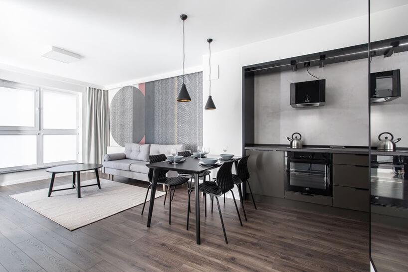 szary aneks kuchenny na tle jasnego salonu zszarą sofąwnętrze apartamentu wgdańskim Dekorian Home projektu Studio Poziom