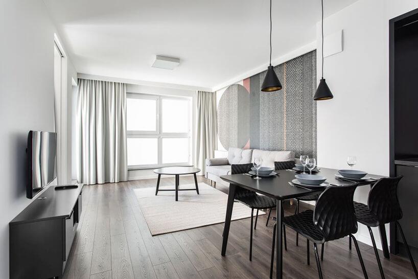 czarny stół zczarnymi krzesłami na tle jasnego salonu zszarą sofa imateriałową tapetą we wnętrzu apartamentu wgdańskim Dekorian Home projektu Studio Poziom
