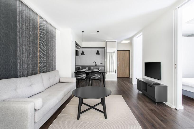 jasny salon zszarą sofa iczarnym stolikiem na tle szarego aneksu kuchennego we wnętrzu apartamentu wgdańskim Dekorian Home projektu Studio Poziom