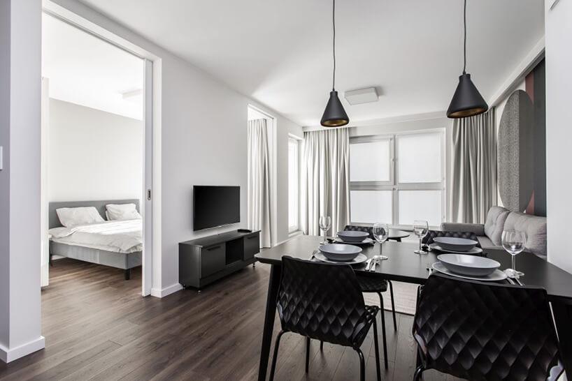 czarny stół zczarnymi krzesłami na tle salonu idrzwiami do sypialni we wnętrzu apartamentu wgdańskim Dekorian Home projektu Studio Poziom