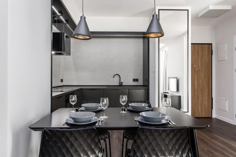czarny stół zzastawą na tle ciemno szarego aneksu kuchennego we wnętrzu apartamentu wgdańskim Dekorian Home projektu Studio Poziom