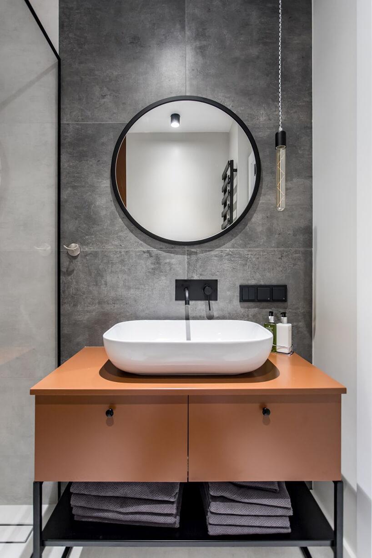 szara łazienka zbrązową szafką pod białą umywalką wolnostojącą we wnętrzu apartamentu wgdańskim Dekorian Home projektu Studio Poziom