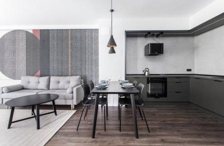 szara kuchnia połączona z salonem z czarnym stołem we wnętrzu apartamentu w gdańskim Dekorian Home projektu Studio Poziom