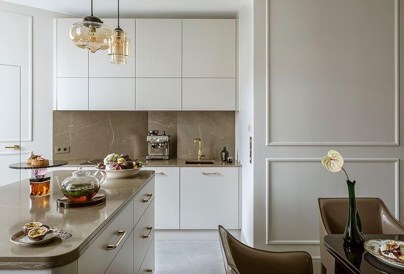 biała nowoczesna kuchnia ze złotymi klamkami przy frontach zbetonowymi beżowymi kaflami