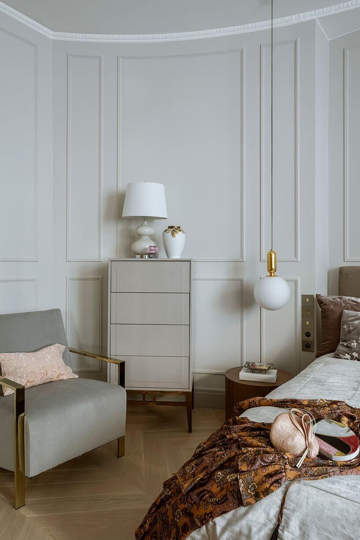 szare ściany wsypialni ze sztukaterią na ścianach przy łóżku oraz fotelu wkolorze szarym