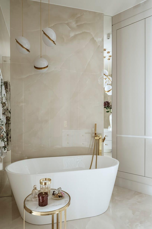 jasna łazienka zbeżem na ścianie iwolnostojącą wanną ze złotymi dodatkami wformie baterii