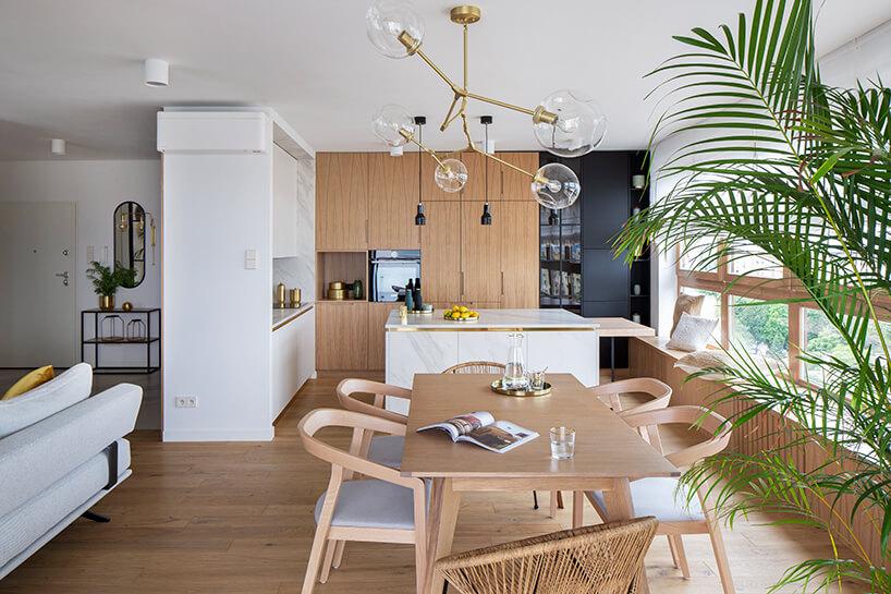 nowoczesny apartament zdrewnianym stołem zsześcioma krzesłami na tle białej wyspy kuchennej ze złotymi akcentami