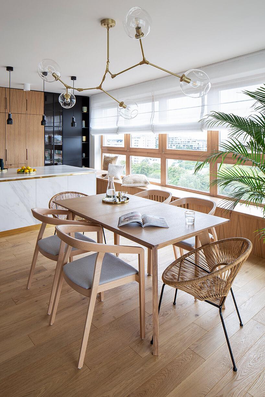 nowoczesny apartament zdrewnianym stołem zsześcioma krzesłami pod wyjątkową złota lampą zprzeźroczystymi szklanymi kloszami