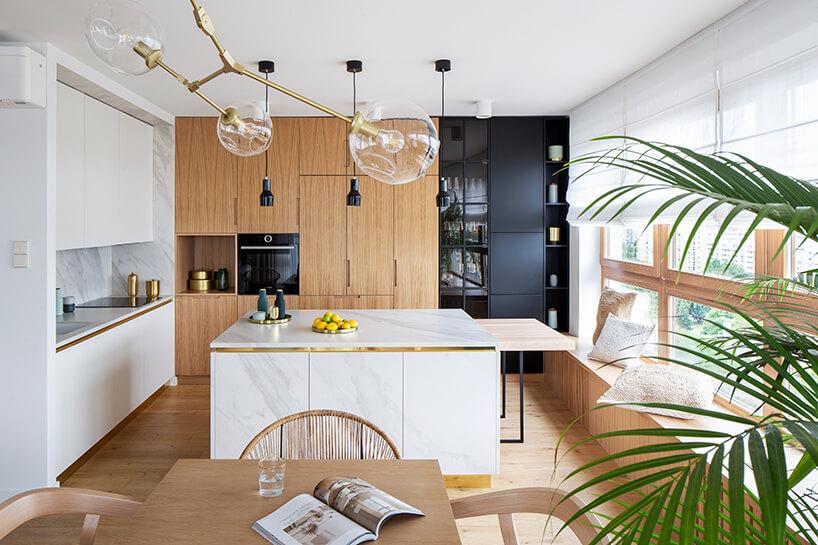 biała wyspa kuchenna ze złotymi elementami na tle brązowych iczarnych frontów zabudowy kuchennej