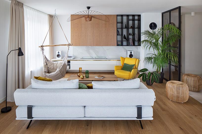 salon wapartamencie zdrewnianą podłogą zjasną sofą na tle wiszącego siedziska iżółtego fotelam