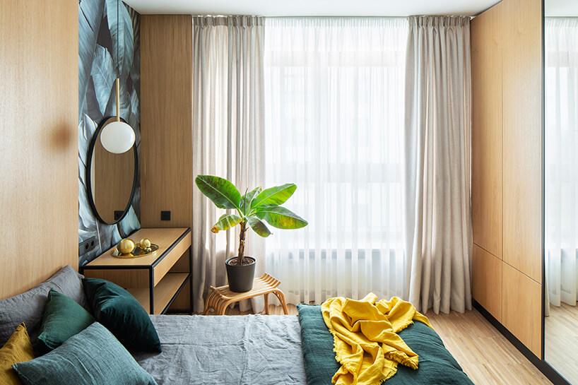 sypialnia wykończona drewnem zkwiecistą tapetą za lustrem wczarnej cienkiej ramie