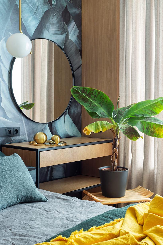 kwiatek na drewnianym siedzisku na tle szafki ze złotymi kulami na blacie