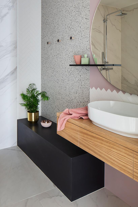 elegancka łazienka zczarną szafką pod drewnianą podwieszaną szafką zbiałą umywalką zdużym lustrem