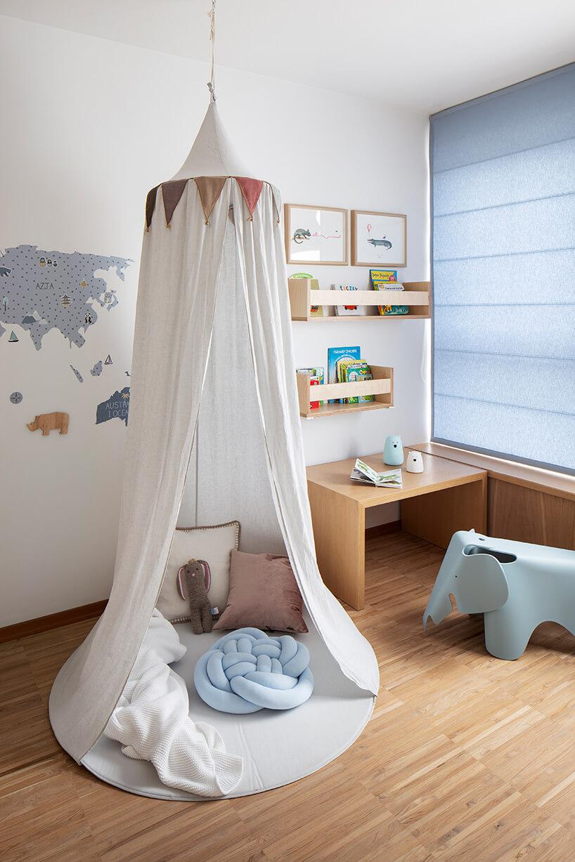 biały pokój dziecięcy zdrewnianą podłogą zniebieskim roletami zpodwieszonym szałase