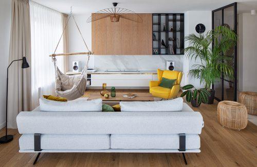 salon w apartamencie z drewnianą podłogą z jasną sofą na tle wiszącego siedziska i żółtego fotelam