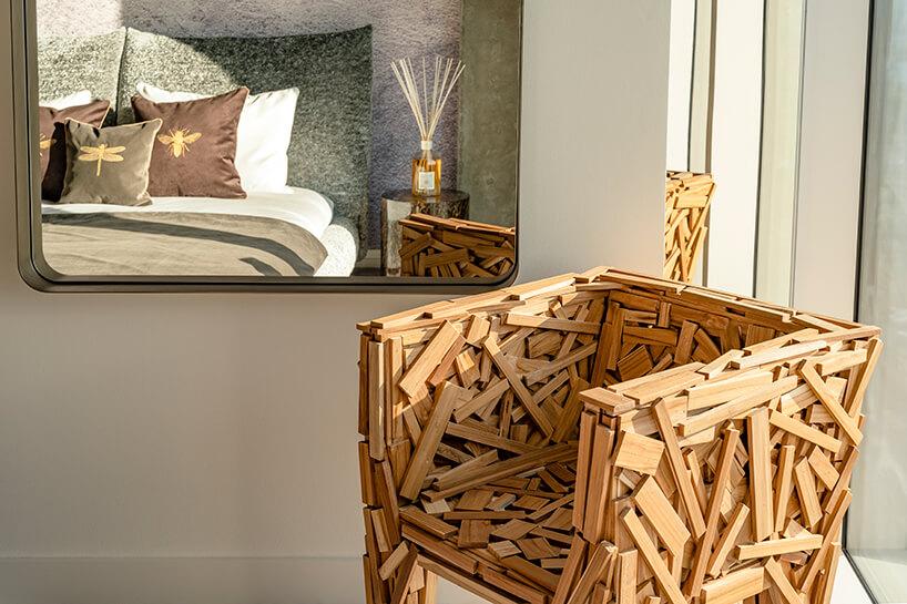 wyjątkowy fotel zdrewnianych deseczek na tle dużego lustra wapartamencie Nature na Złotej 44