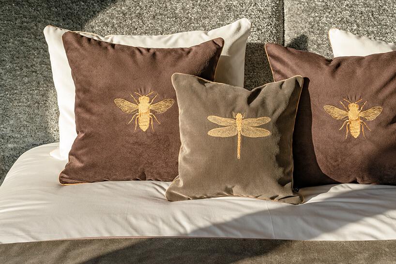 wyjątkowe ciemne poszewki ze złotymi wyszytymi owadami na łóżku wapartamencie Nature na Złotej 44