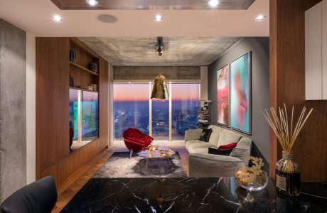 stół z czarnym kamiennym blatem na tle szarej sofy i czerwonego eleganckiego fotela na tle widoku na Warszawę w apartamencie Nature na Złotej 44
