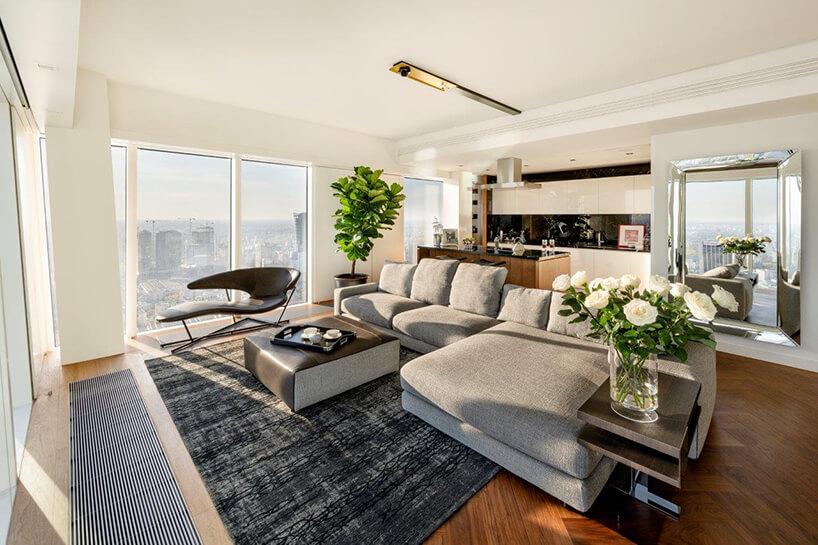 nowoczesny apartament projektu Anny Koszeli zdużą szarą sofą na tle biało czarnego aneksu kuchennego