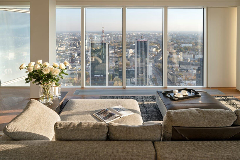 nowoczesny apartament projektu Anny Koszeli szara sofą na tle wysokich okien zwidokiem na wieżowce Warszawy