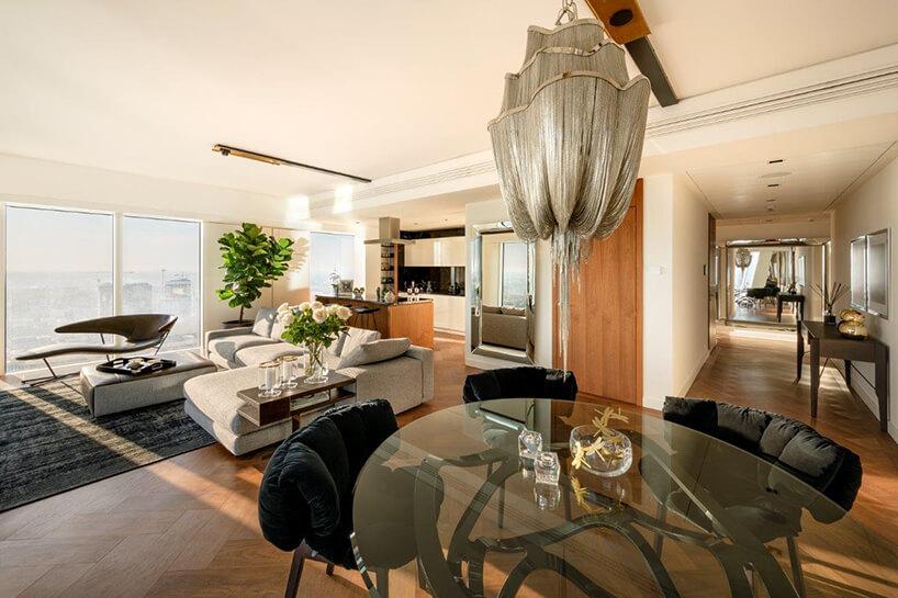 wyjątkowy srebrny żyrandol nowoczesnym apartamencie projektu Anny Koszeli nad szklanym stołem ztrzema krzesłąmi zczarnym siedziskiem ioparciem