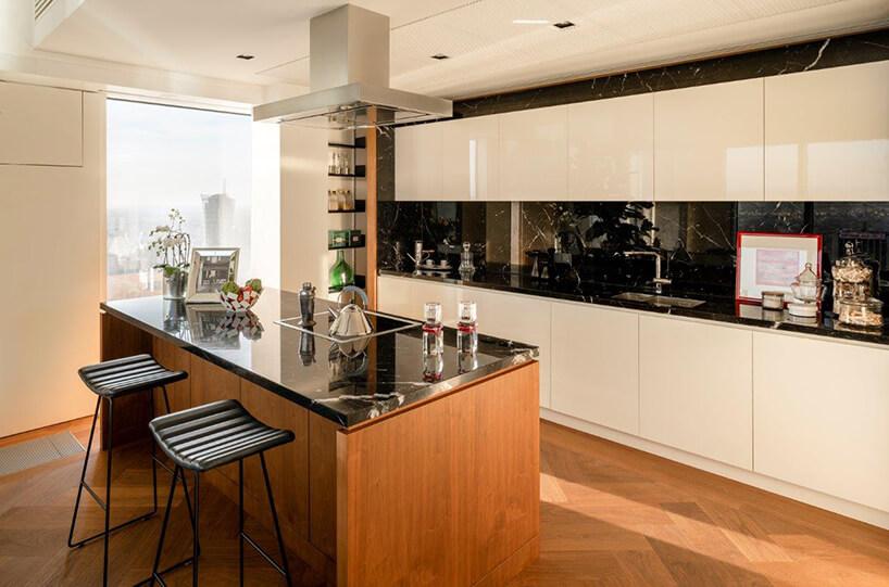 mała drewniana wyspa kuchenna zczarnym kamiennym nowoczesny apartament projektu Anny Koszeli na tle kuchni zbiałym frontami szafek iczarnym kamiennym blatem wraz zczarną kamienną ścianą