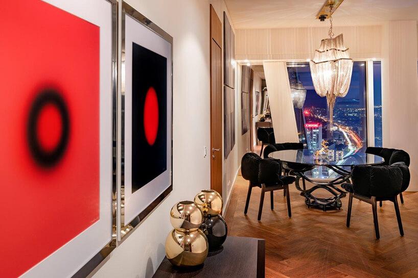dwa czarno czerwone plakaty wsrebrnych błyszczących ramach wnowoczesnym apartamencie projektu Anny Koszeli przy dwóch złotych wazonach na drewnianej komodzie