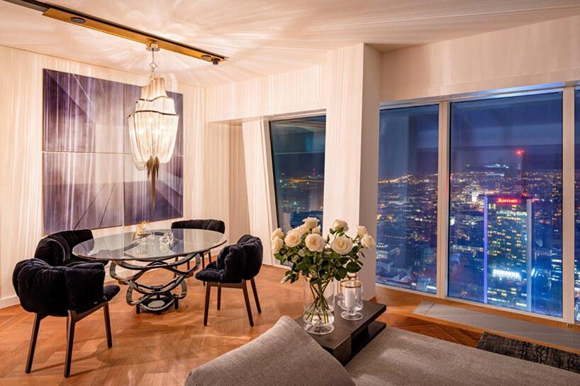 nowoczesnych stół ze szklanym blatem wnowoczesnym apartament projektu Anny Koszeli pod wyjątkowym żyrandolem na tle obrazu obok widoku na rozświetloną nocną Warszawę