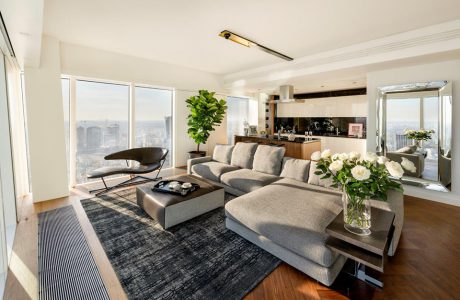 nowoczesny apartament projektu Anny Koszeli z dużą szarą sofą na tle biało czarnego aneksu kuchennego na Złotej 44