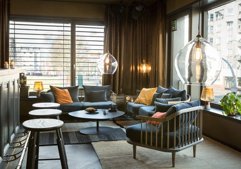eleganckie wnętrze apartamentu wstylu Bohema od Wnętrza Michała nisko zawieszony lampy zdużymi szklanymi kloszami