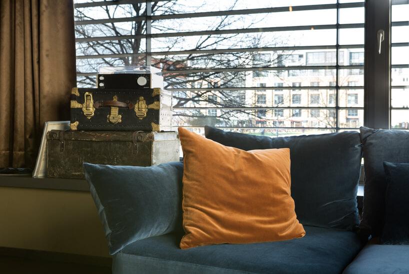 eleganckie wnętrze apartamentu wstylu Bohema od Wnętrza Michała niebieska sofa obok szafki ze starymi walizkami