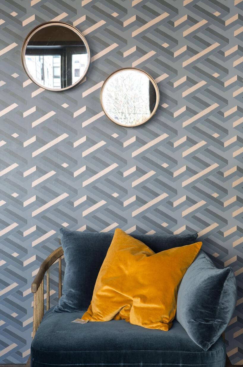 eleganckie wnętrze apartamentu wstylu Bohema od Wnętrza Michała niebieski fotel zżółtymi iniebieskimi poduszkami na tle ściany niebieską tapetą