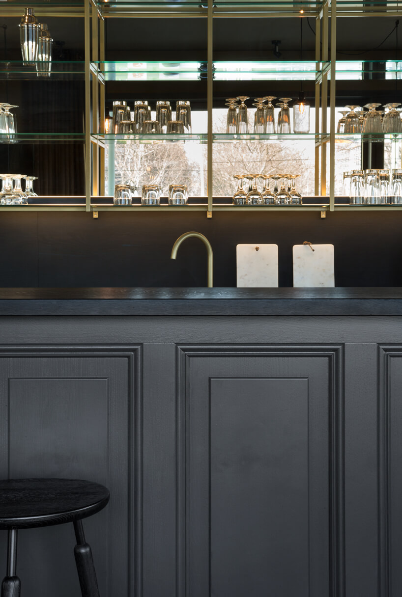 eleganckie wnętrze apartamentu wstylu Bohema od Wnętrza Michała ciemna wyspa na tle szafki ze złotym stelażem