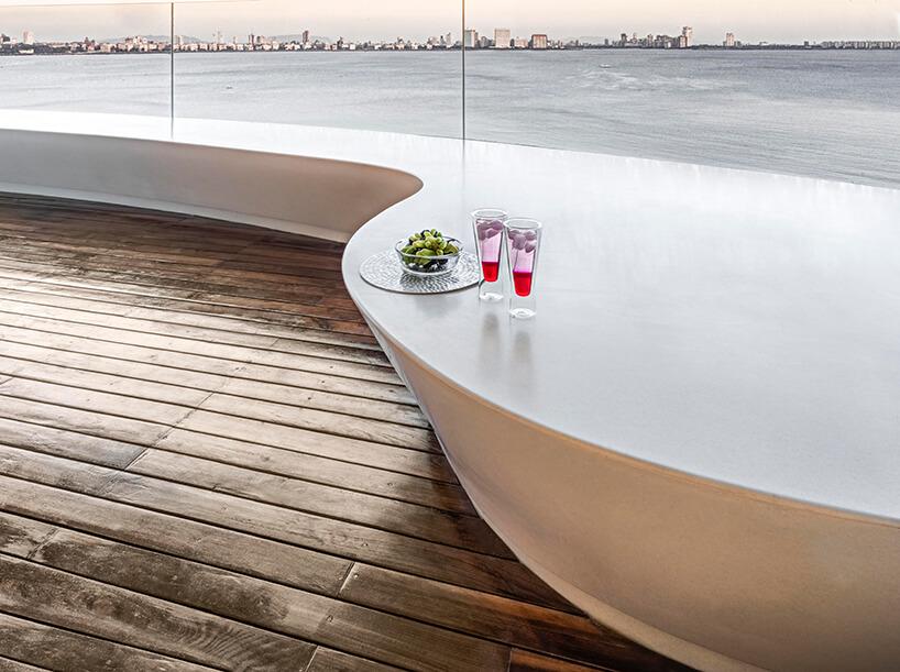 ekskluzywny apartament projektu ZZ Architects drewniany taras zdługim białym siedziskiem na tle rzeki zzarysem miasta