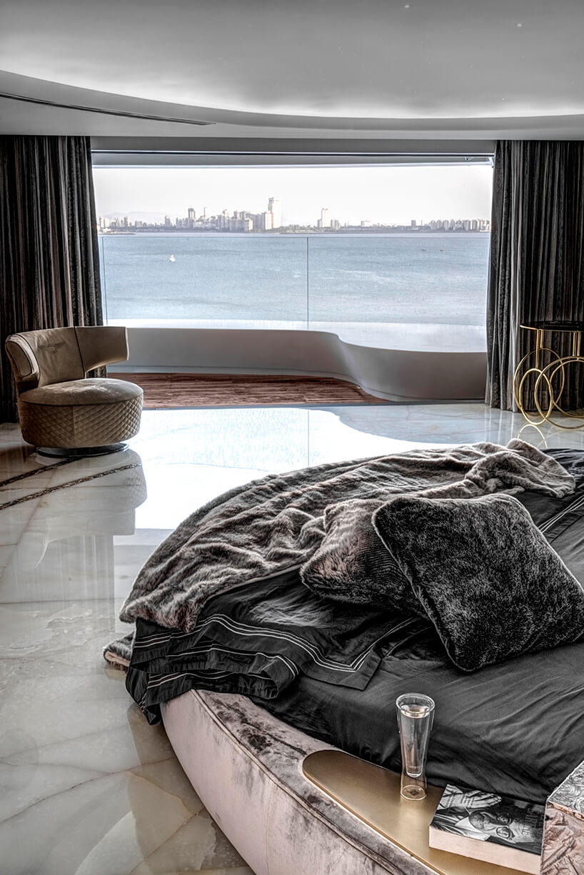 ekskluzywny apartament projektu ZZ Architects sypiania zokrągłym jasnym łóżkiem idużym panoramicznym oknem zwidokiem na rzekę