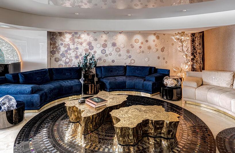 ekskluzywny apartament projektu ZZ Architects salon zdwoma złotymi stolikami onieregularnym kształcie przy białej iniebieskie okrągłej sofie na mozaikowej podłodze