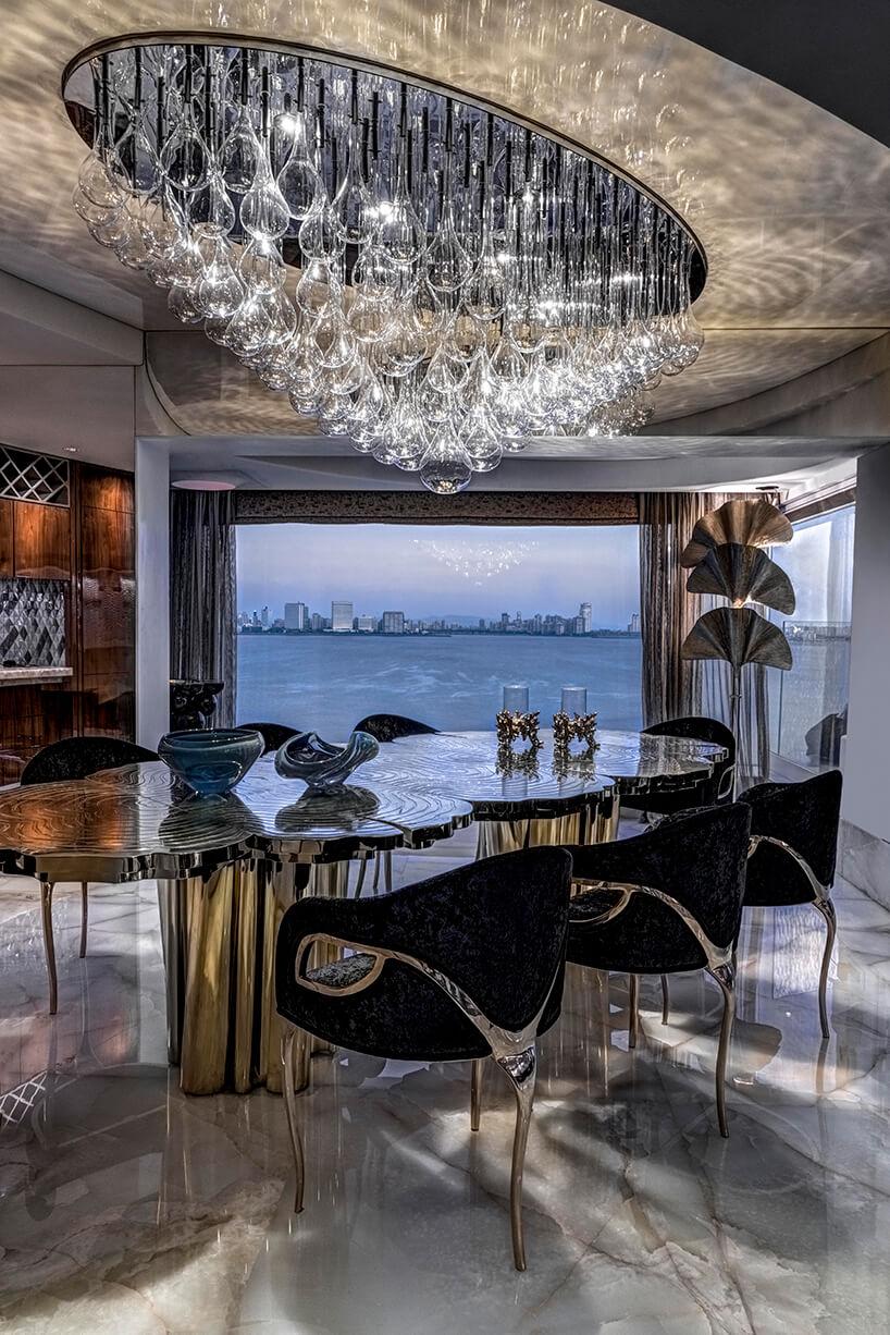 ekskluzywny apartament projektu ZZ Architects jadalnia zwyjątkowym błyszczącym stołem iczarnym krzesłami na trzech nogach zwidokiem na rzekę