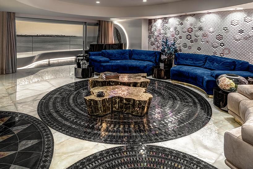 ekskluzywny apartament projektu ZZ Architects salon zdwoma złotymi stolikami onieregularnym kształcie na tle niebieskie okrągłej sofy na tle jasnej ściany zsześciokątnych płytek