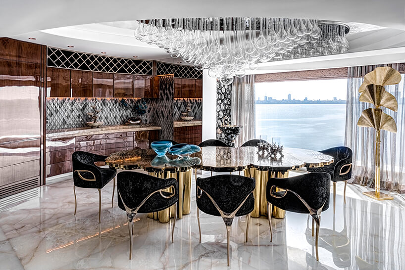 ekskluzywny apartament projektu ZZ Architects jadalnia zwyjątkowym błyszczącym stołem iczarnym krzesłami na trzech nogach