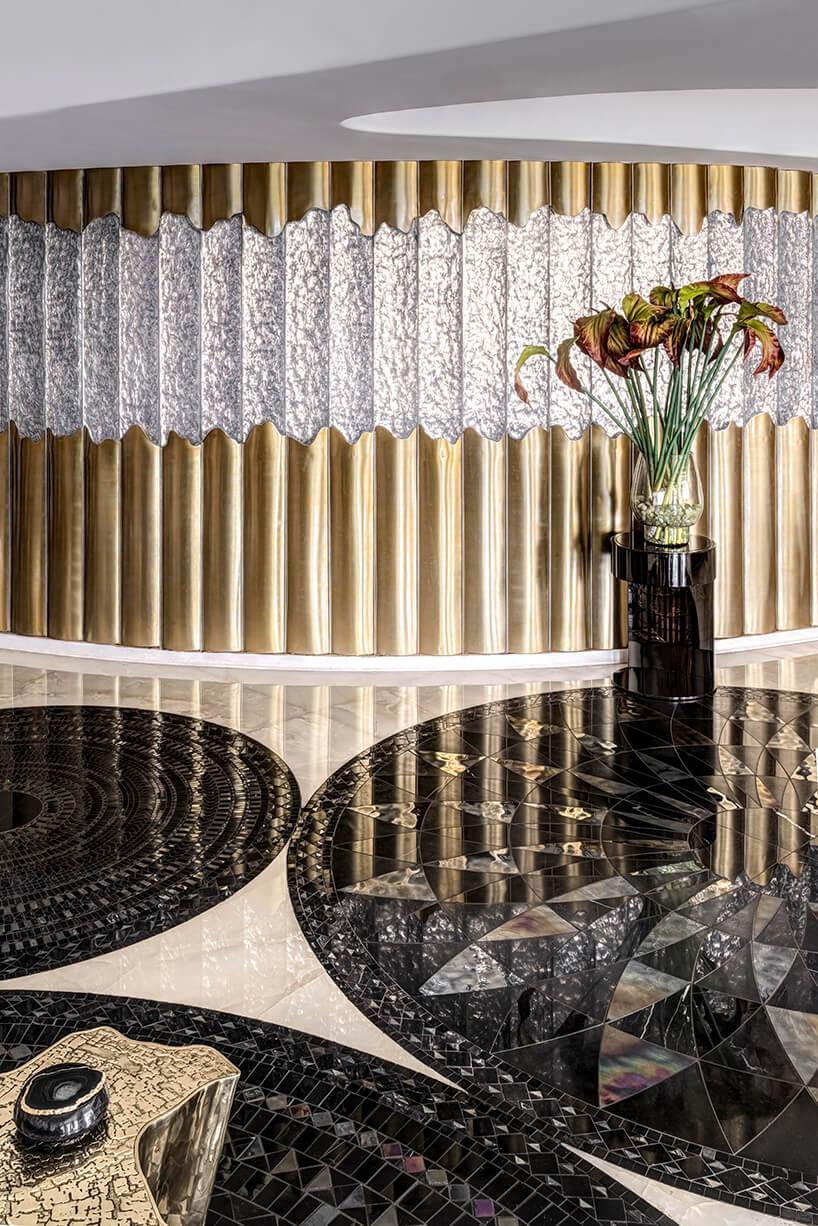 ekskluzywny apartament projektu ZZ Architects salon ze ścianą zze złotych paneli przedzielonych srebrnymi elementami przy mozaikowej podłodze wciemne okręgi