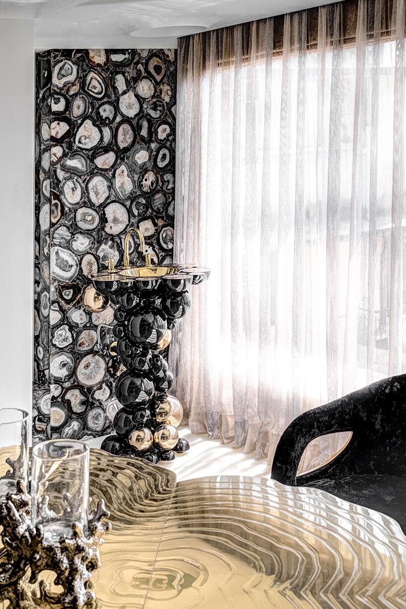 ekskluzywny apartament projektu ZZ Architects czarna błuszcząca umywalka zczarnych izłotych kul na tle ciemnej ściany zciętego kamienia