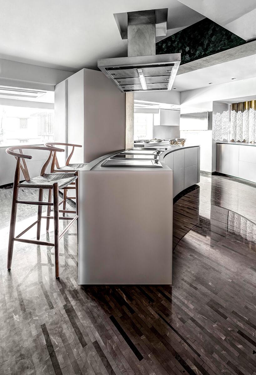 ekskluzywny apartament projektu ZZ Architects białe kuchnia zzaokrągloną biała wyspą na ciemnej podłodze zcienkich długich pasków kamieni