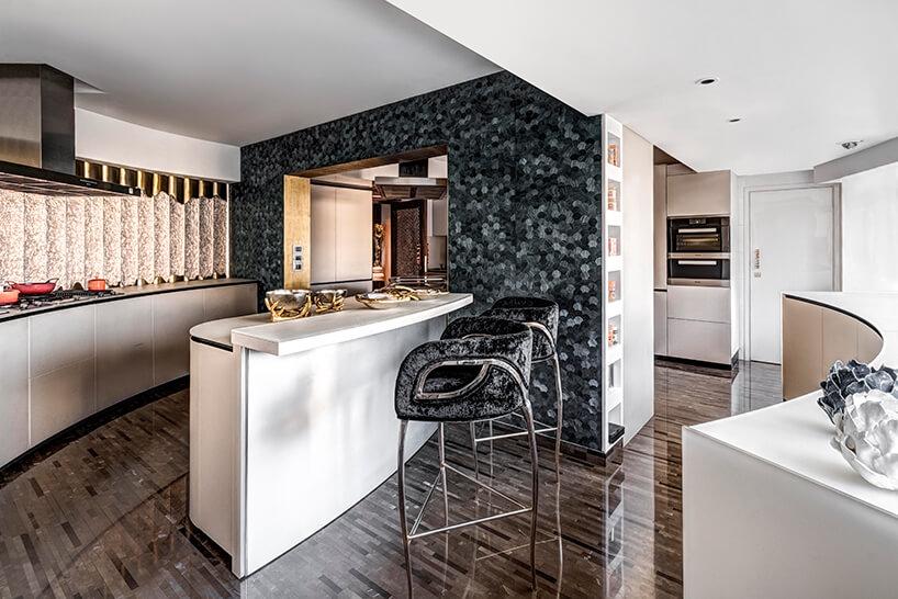 ekskluzywny apartament projektu ZZ Architects kuchnia zbiałą wyspą na tle ciemnej ściany mozajkowej