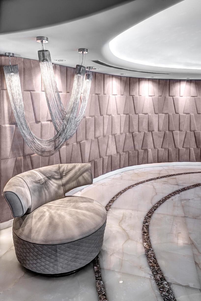 ekskluzywny apartament projektu ZZ Architects biały elegancki fotel na białej podłodze zkamienia zciemnym owalnym paskiem na tle różowej ściany zelementów przestrzennych