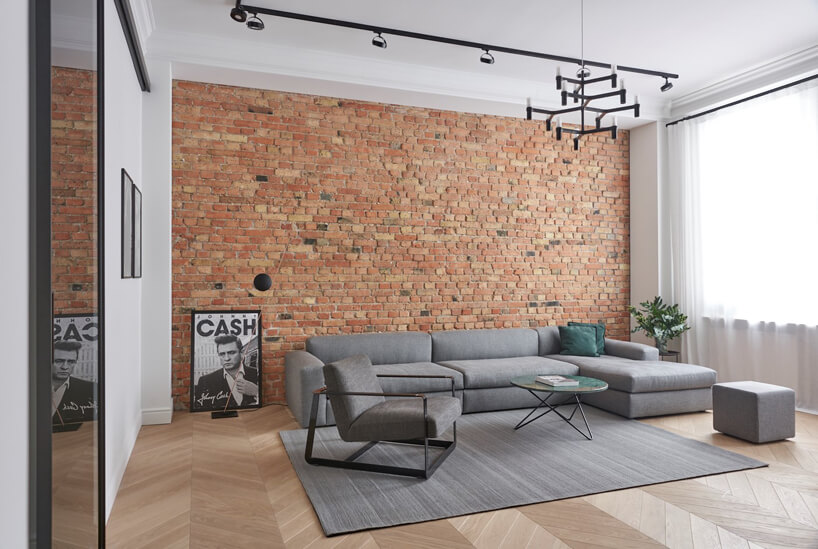 salon wapartamencie szarymi meblami do siedzenia na tle ceglanej ściany