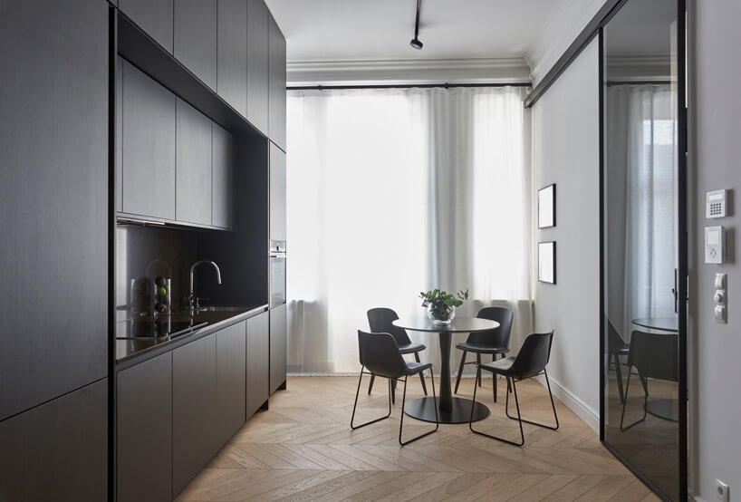 mała kuchnia zciemnymi meblami imałym stolikiem zczterema krzesłami