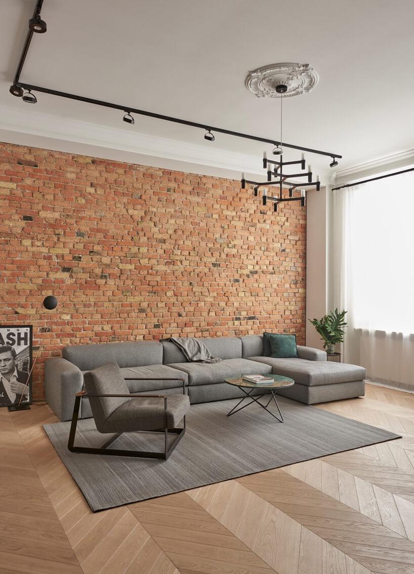 salon wapartamencie szarymi meblami do siedzenia na tle ceglanej ściany zplakatem